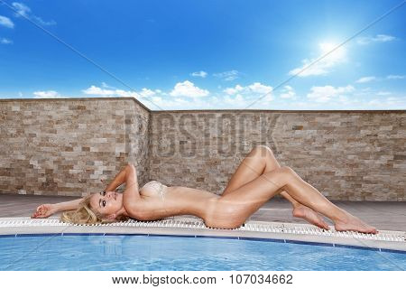 Beautiful Blonde Sexy Woman Model Lying On A Blue Pool Of The View Of The Sea And Mountains, Rocks