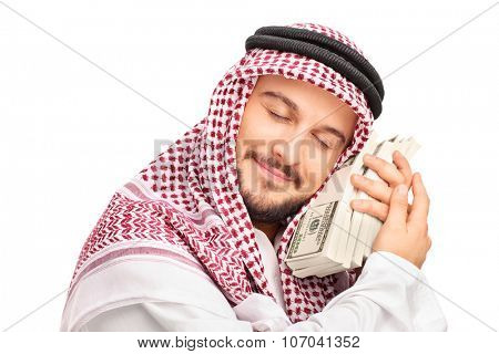 Close-up on a young male Arab person sleeping on money and smiling isolated on white background