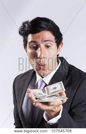 businessman blowing at money from his hands (isolated on gray)