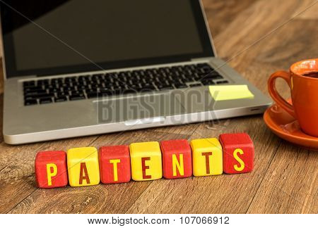 Patents written on a wooden cube in front of a laptop