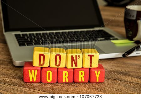 Don't Worry written on a wooden cube in front of a laptop