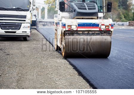 Road Works, Asphalting And Laying Fresh Bitumen During Construction Works. Industrial Heavy Duty Com