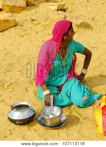 JAISALMER INDIA - FEBRUARY 18: Unidentified woman sits on a sand in traditional village on February 18 2011 in Thar Desert India. Thar Desert forms natural boundary running along the border between India and Pakistan.