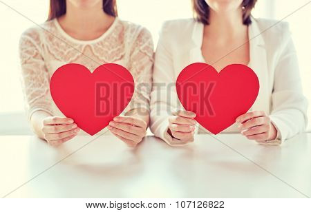 people, homosexuality, same-sex marriage, holidays and love concept - close up of happy lesbian couple holding red paper hearts