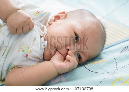 Asian Baby Sleeping Is Suck White Bed Linen.