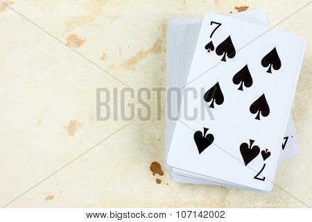 A poker card deck with seven of spades on the top poster