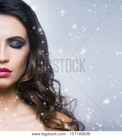 Beauty portrait of a young and gorgeous woman over Christmas background.