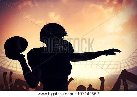 Silhouette American football player throwing ball against football stadium with cheering crowd