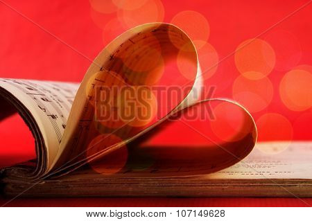 Music Notation Book With Pages Shaping Heart On Red With Bokeh Soft Lights