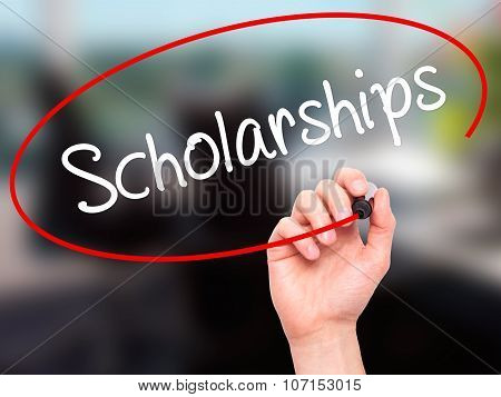 Man Hand writing Scholarship with black marker on visual screen