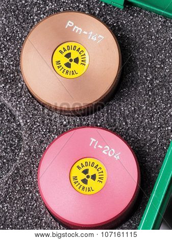 Two specialist containers with warning sticker and engraving containing radioactive isotopes
