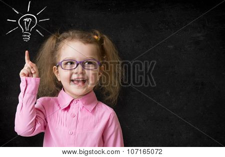 kid in glasses with idea lamp on school chalkboard