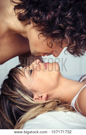 Young man kissing to beautiful woman lying on bed