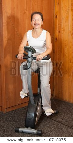 Woman Working Out On Exercycle At Home