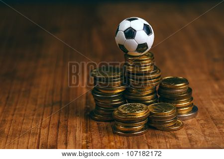 Soccer bet concept with small football on top of coin stack making money by predicting sport results. poster