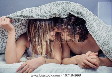 Happy young couple in love kissing under duvet cover