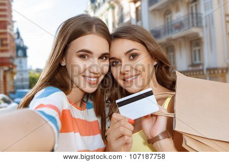 Two friends doing selfie with shopping bags