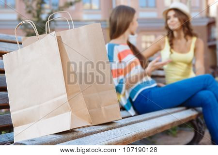 Two friends relaxing on a bench during shopping