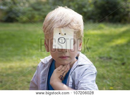Surprising Boy Sits On Green Grass In Forest. Concept Of Happy Thoughts And Positive Emotions.