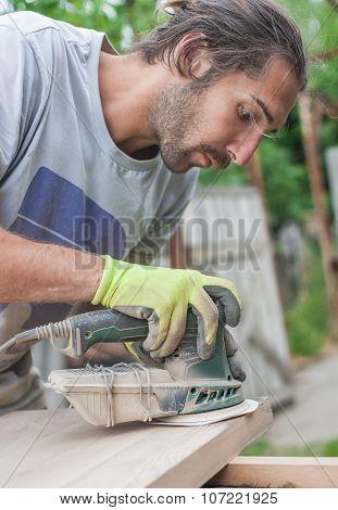 Carpenter Using Electric Sander