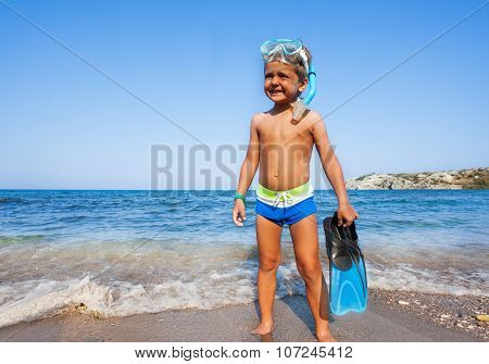 Boy with scuba mask, paddles standing on seashore