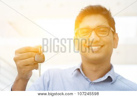 Young Asian Indian estate agent or salesman showing a key, India male business man, real modern office building with morning sunlight as background.