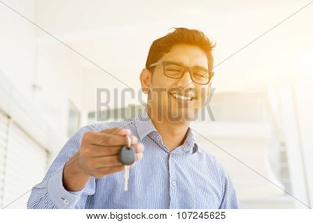 Asian Indian estate agent or salesman showing a key, India male business man, real modern office building with morning sunlight as background.