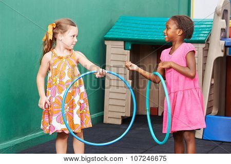 Two children playing together with hula hoops in preschool