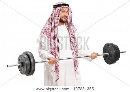 Young male Arab in a white robe and checkered veil exercising with a barbell isolated on white background