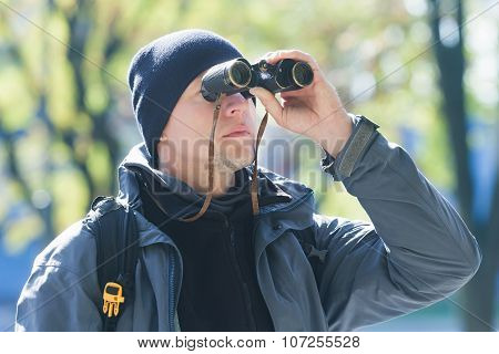 Young Man With Binoculars Bird Watching At Demi-season Natural Background