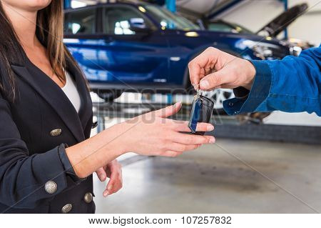 Customer gets the carkeys from mechanic after the maintanace of her vehicle
