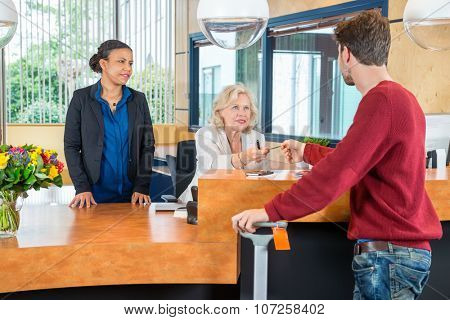 Man paying through credit card at hotel front desk