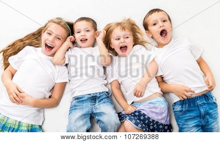 children in white shirts lying on the floor isolated on white background