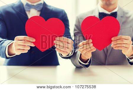 people, homosexuality, same-sex marriage, valentines day and love concept - close up of happy married male gay couple holding red paper heart shapes on wedding poster