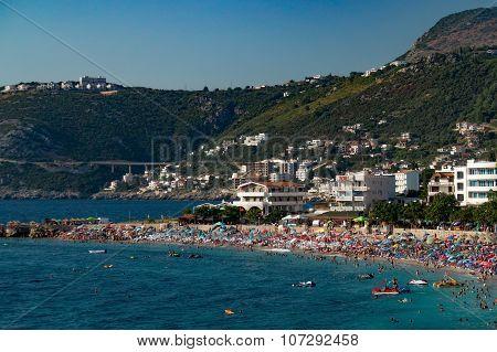 Populous beach in resort near mountains