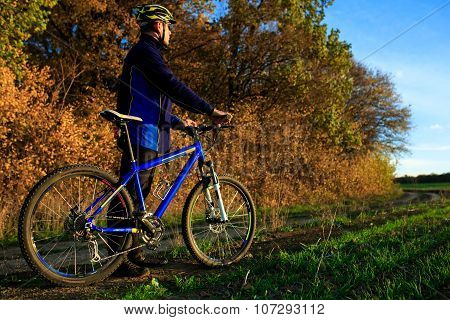 sports activity: young adult cyclist riding mountain bike in the countryside. Horizontal shape, side view, copy space poster