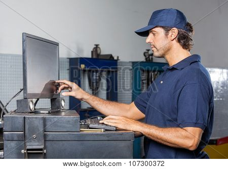 Side view of male mechanic using computer in auto repair shop