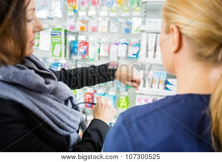 Mid adult female customer showing smartwatch to chemist in pharmacy