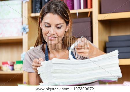 Mid adult female worker analyzing papers in shop