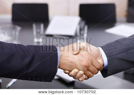 Apretón de manos de los empresarios sobre la mesa