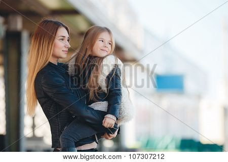 Mother holding daughter in her arms,standing in the fresh air