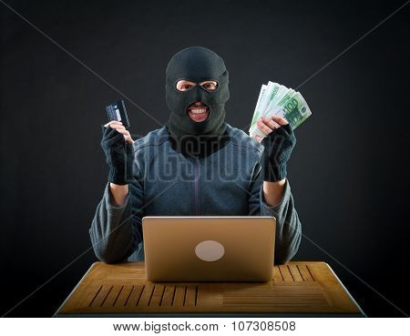Happy cybercriminal man holding euro cash and stolen credit card
