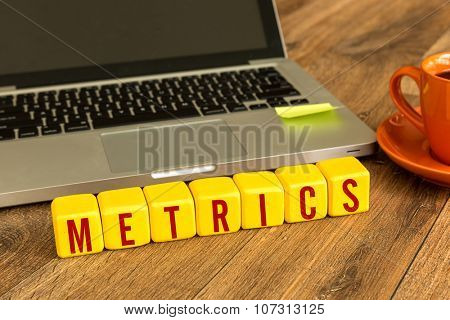 Metrics written on a wooden cube in front of a laptop