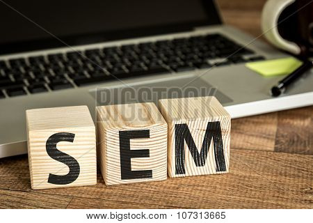 SEM (Search Engine Marketing) written on a wooden cube in a office desk