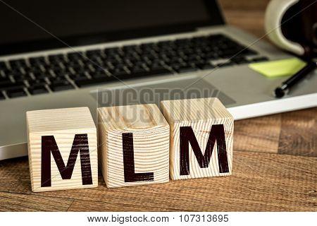 MLM (Multi-Level Marketing) written on a wooden cube in a office desk