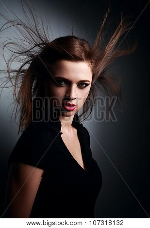 Wild Expressive Young Woman With Wind Hairstyle And Vamp Look On Dark