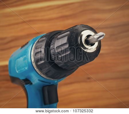 electric drill with drill bit on a wooden background poster