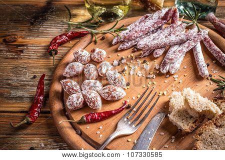 Mini salami and salami sticks on wooden sutting board poster