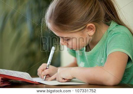 Pre-adolescent Girl Concentrates On Her Studies