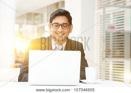 Young Asian Indian business man using a laptop or notebook computer at cafe, with a cup of coffee. India male business man, modern building with beautiful golden sunlight as background.